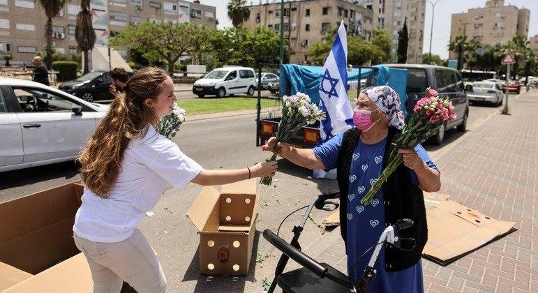 Mulher israelense entrega flor a idosa após anúncio de cessar-fogo