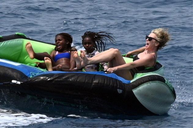 De férias na Grécia com as filhas, Charlize Theron parece estar realmente se divertindo. A atriz foi fotografada dando risada com as meninas enquanto elas estavam em uma enorme boia, puxada por um barco em alta velocidade