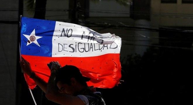 Protesto no Chile: manifestante segura bandeira contra a desigualdade