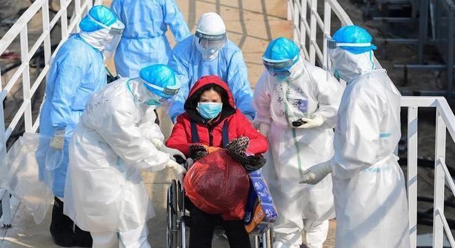 Profissionais de saúde transportam paciente infectada pelo coronavírus em Wuhan