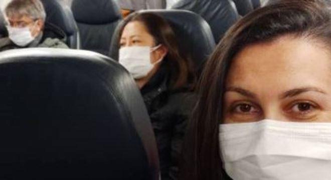 A brasileira Indira Mara Santos, uma das repatriadas, faz selfie dentro do avião