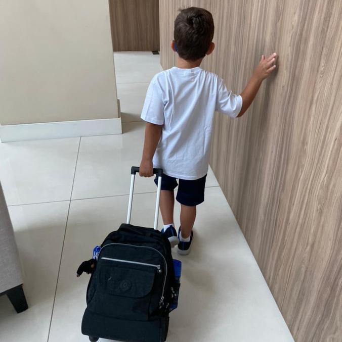Theo na volta às aulas presenciais: alcool gel pendurado na mochila