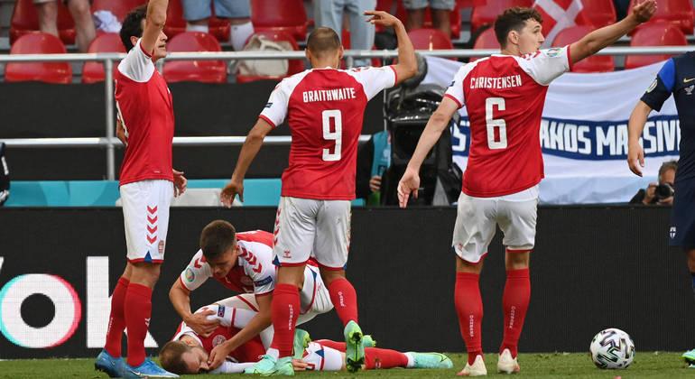 Christian Eriksen é amparado por colegas de time durante mal súbito que sofreu no jogo
