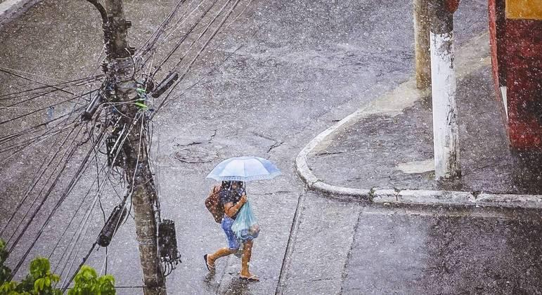 Pedestre tenta se proteger da chuva no bairro Saúde, na zona sul de São Paulo