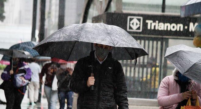 Pedestres se protegem da chuva na avenida Paulista