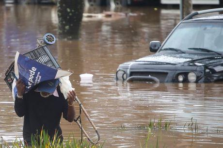 Morador atravessa área inundada na zona oeste de SP