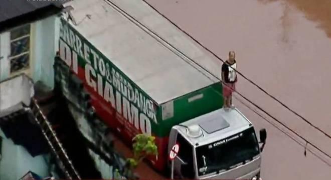 Homem sobe em caminhão para escapar da enchente, em SP