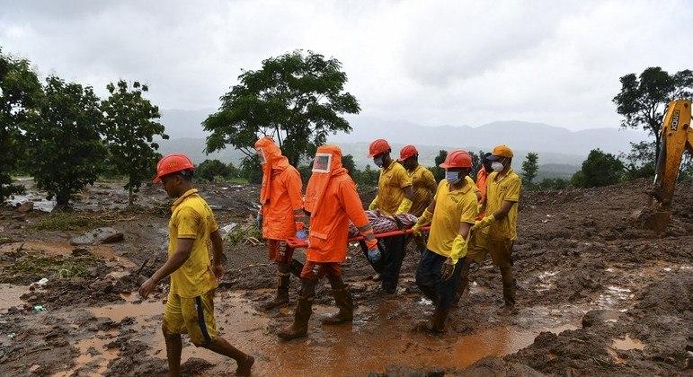 Equipe de resgate trabalham para localizar vítimas entre a lama e os escombros