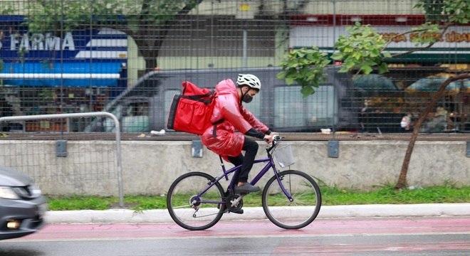 Ciclista pedala sob chuva em SP