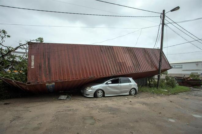 As perdas econômicas também devem ser enormes. Na foto, pode se ver um carro embaixo de um contêiner que foi derrubado pela força dos ventos do ciclone