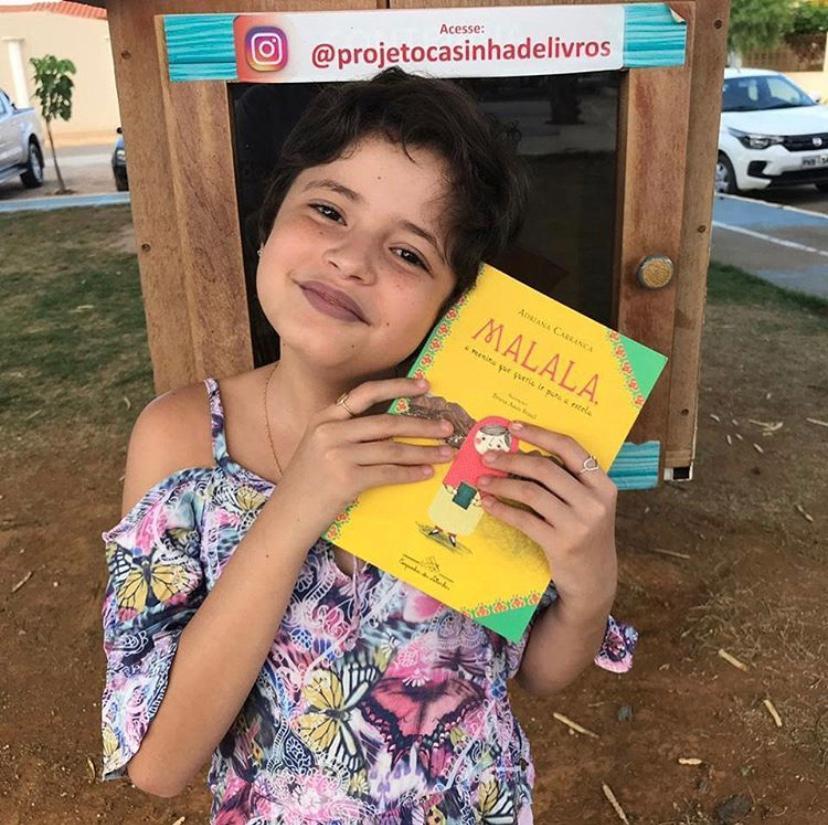 Clara Beatriz segura o livro que inspirou a criação do projeto das casinhas de livros
