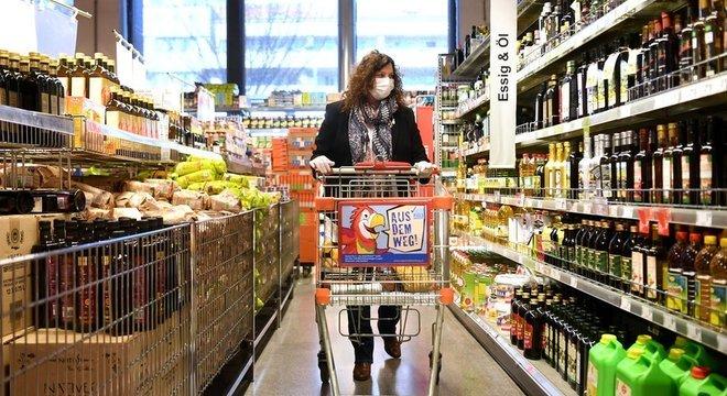 Clientes usam máscaras protetoras em supermercado em Viena.