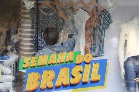Comerciante arruma vitrine com cartaz da campanha