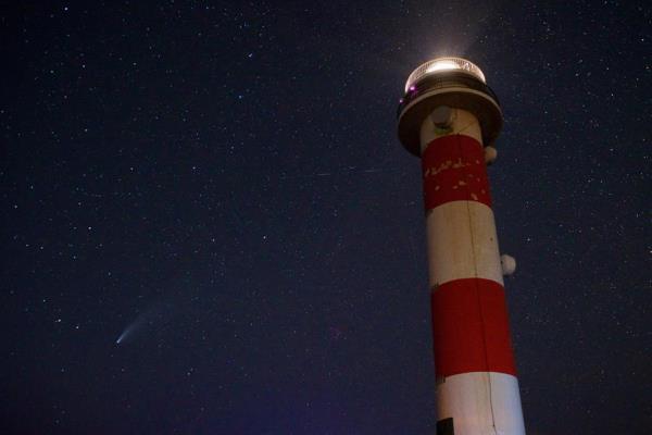 Também na Espanha, uma foto do cometa em uma observação próxima do farol El Tostón, na cidade de El Cotillo