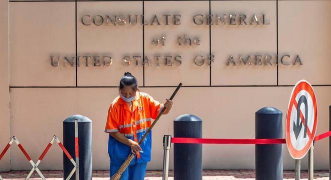 Trabalhadora limpa calçada em frente ao Consulado fechado dos EUA em Chengdu, China