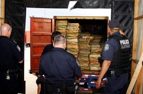 Policiais abrem um dos 7 contêineres com cocaína