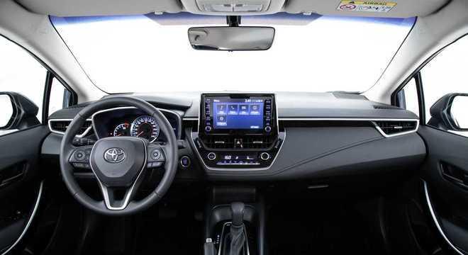 Interior retilíneo do Corolla: na versão GLI quase tudo é preto, freio tem alavanca e bancos em tecido