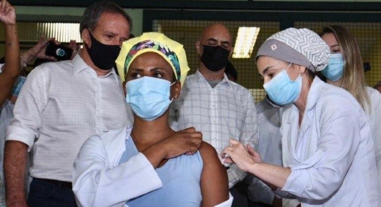 Helen Cristina, de 46 anos, técnica de enfermagem, recebe a primeira dose da CoronaVac aplicada pelo sistema municipal de saúde de SP