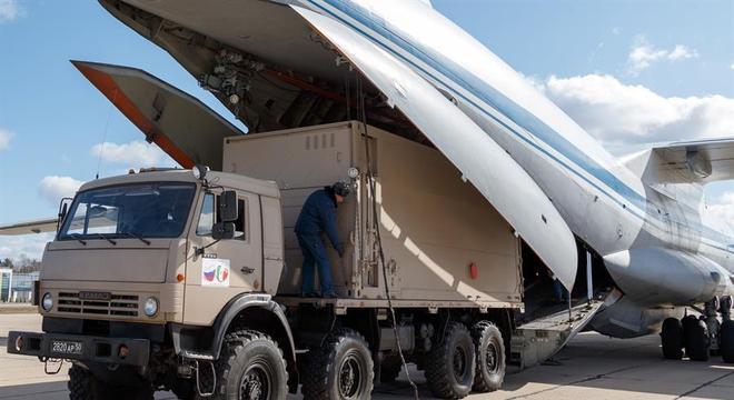Veículo militar russo é embarcado em avião em Moscou, para ser levado à Itália