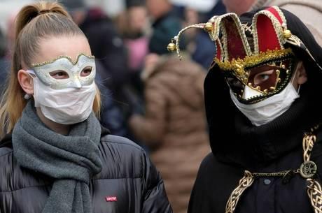 Turista usa máscara cirúrgica e de carnaval, em Veneza, Itália.