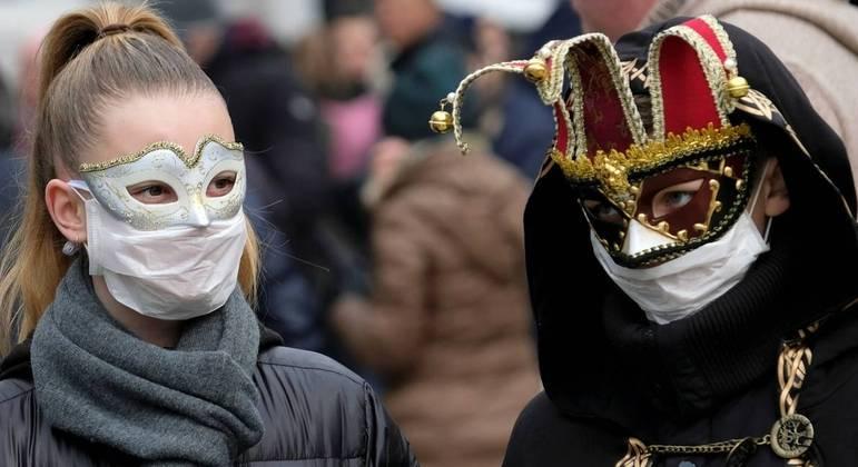 Turistas usam máscara cirúrgica durante o carnaval de Veneza por conta do coronavírus em 2020