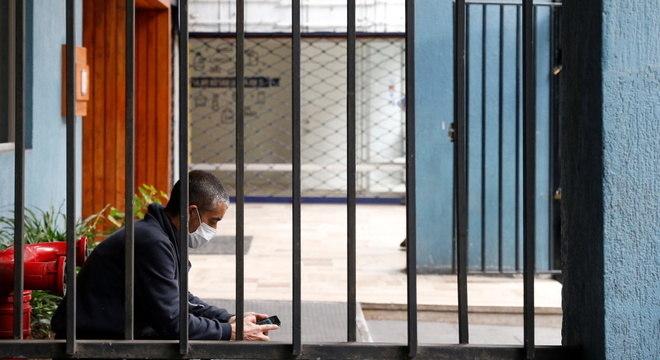 Homem com máscara sozinho em prédio no Chile, durante a pandemia