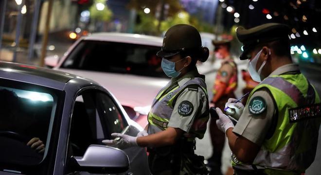 Policiais fiscalizam o toque de recolher em Santiago, capital do Chile