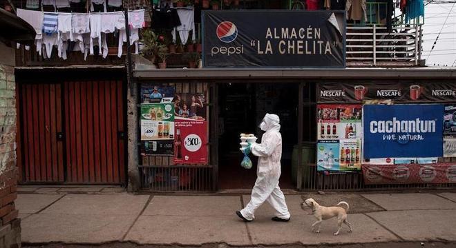Moradora de Santiago do Chile entrega comida a famílias pobres durante a pandemia