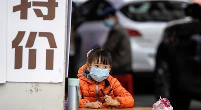 Menina nas ruas de Guagnzhou; China não tem mortes por covid-19 desde o dia 14/4