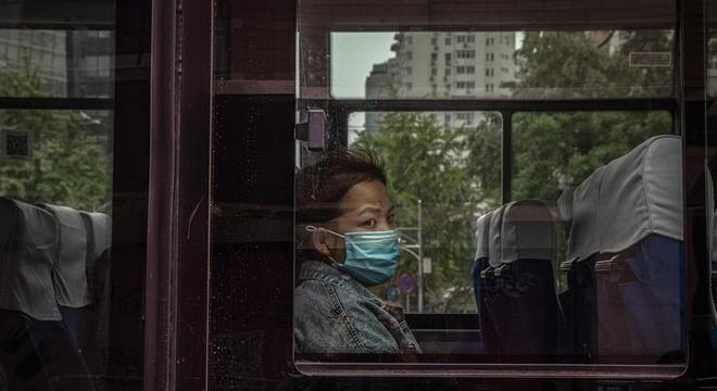 Mulher viaja de ônibus em Pequim usando máscara de proteção