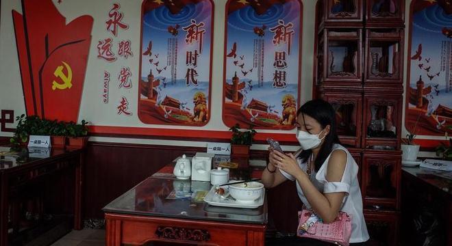 Mulher usa máscara em restaurante em Pequim, China