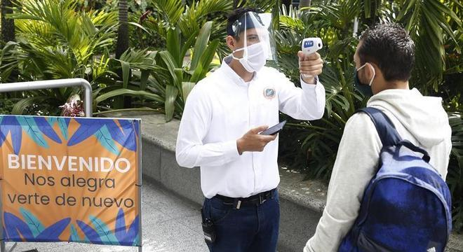 Funcionário mede temperatura de cliente de shopping reaberto em Medellín, na Colômbia
