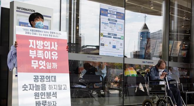Médico em greve segura cartaz na porta de um hospital em Seul, na Coreia do Sul