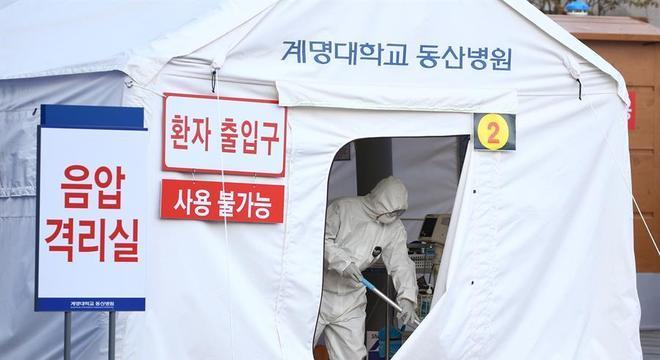 Profissional de saúde monta tenda para isolamento de pacientes com coronavírus em Daegu