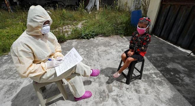 Médico entrevista criança em Quito durante levantamento de casos de covid-19
