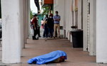 Pessoas observam corpo de homem que morreu na calçada em Guayaquil, Equador