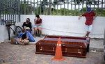 Famílias aguardam em calçada o recolhimento de caixões com vítimas de covdi-19