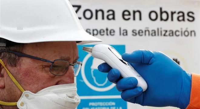 Trabalhador espanhol tem a temperatura medida ao retonar ao trabalho
