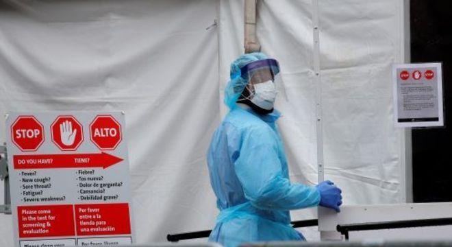 Agente de saúde com traje de proteção entra em hospital em Nova York
