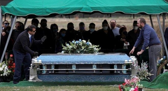 Familiares de vítima da covid-19 acompanham enterro no Colorado (EUA)
