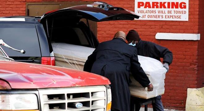 Caixão de vítima da covid-19 é posto em carro funerário em Nova York