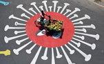 Vendedor de côco passa com seu triciclo sobre grafiti do coronavírus pintado em rua de Chennai, na Índia