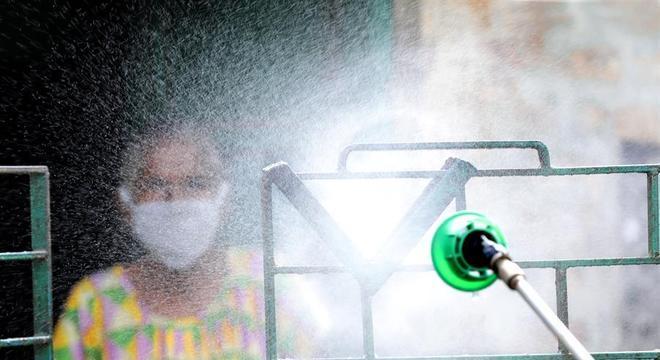 Casa e moradora passam por desinfecção contra o coronavírus em Kolkata, na Índia