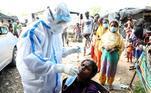 Trabalhador da saúde coleta material para testes de covid-19 em mulheres da cidade de Jammu, na Índia