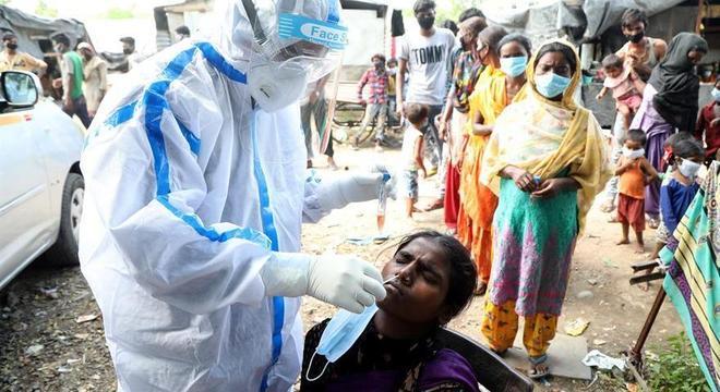 Trabalhador da saúde coleta material para testes de covid-19 na cidade de Jammu, na Índia