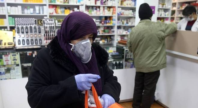 Mulher com máscara e luva de proteção contra o coronavírus em farmácia de Teerã, no Irã