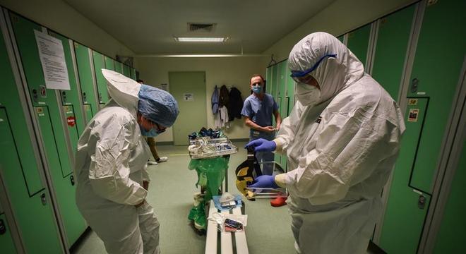 Médicos e enfermeiras vestem roupas de proteção em um hospital de Milão