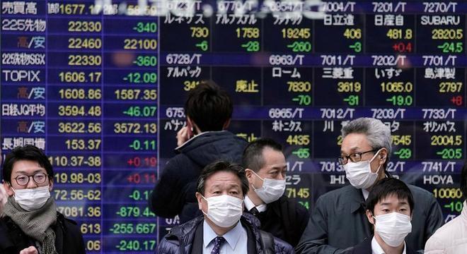 Homens usam máscara em frente a painel da bolsa de valores de Tóquio