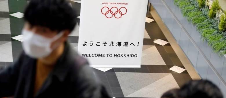 Pessoas com máscara para evitar contaminação por coronavírus em um prédio de Hokkaido, Japão, com cartaz das Olimpíadas de Tóquio ao fundo
