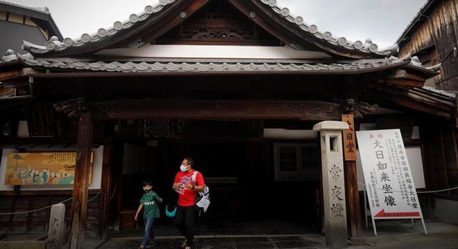 Homem e criança usam máscara ao deixarem templo em Kyoto, no Japão